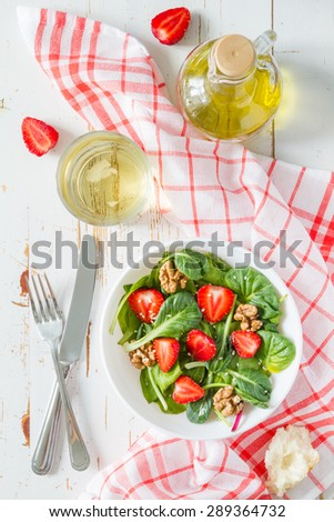 Strawberry salad with spinach, nuts, cheese in white bowl, plaid napkin, white wood background, top view - stock photo