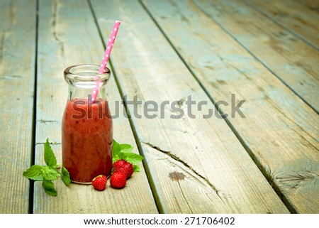Strawberry smoothie freshly made in a jar with a straw on rustic wood - stock photo