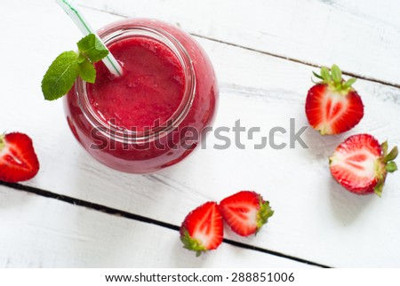 Strawberry smoothie in a glass jar with green ribbon at the white table. Top view - stock photo
