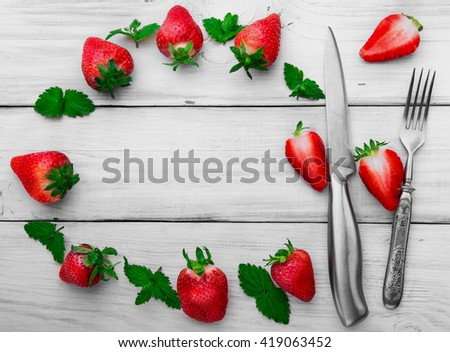 Strawberry, stainless stell knife and fork , leaf of mint slice of strawberry.White wooden background.Free space in the middle.Round composition - stock photo