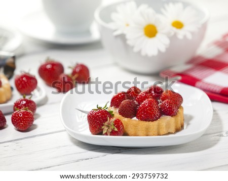 Strawberry tartlet on plate with fork, on coffee table, marguerite daisies in background - stock photo