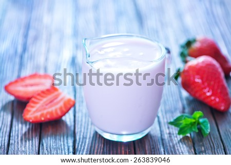 strawberry yogurt in glass jug and on a table - stock photo