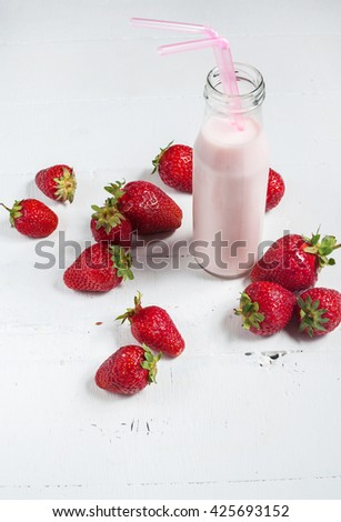 Strawberry yogurt with fresh strawberries on a white wooden background.
