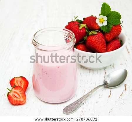 Strawberry yogurt with fresh strawberries on a wooden background - stock photo