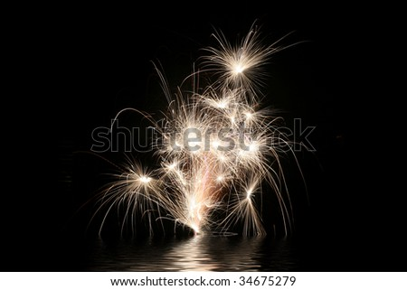 Streaking fireworks over water background with night sky - stock photo