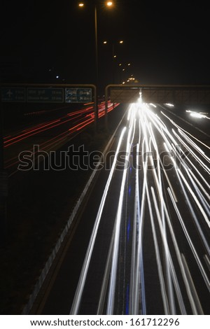 Streaks of headlights of moving vehicles on the road, National Highway 8, Gurgaon, Haryana, India
