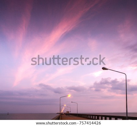 Streaks of red clouds at sunset on a pier with street lights in east Thailand. Travellers to Ko Kut depart from here.