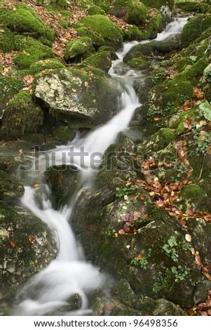 Stream A fresh stream flowing between rocks - stock photo