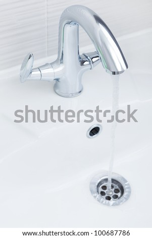 Stream and drops of pure water in a sink - stock photo