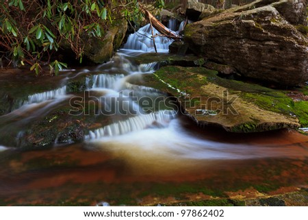 Stream and waterfalls in spring in the mountains - stock photo