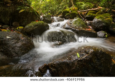 stream flowing water over rocks at a little falls - stock photo