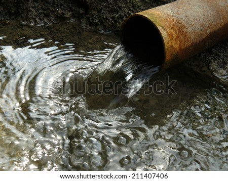 stream of artesian water from the old rusty pipe - stock photo