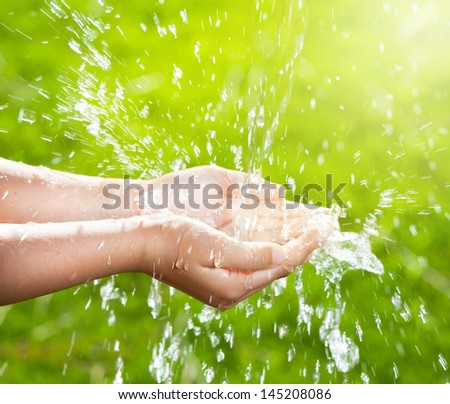 Stream of clean water pouring into children's hands. - stock photo
