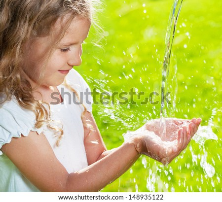 Stream of clean water pouring into children's hands. Child play with water - stock photo