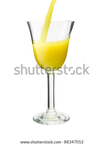 Stream of orange juice falling in a chic glass