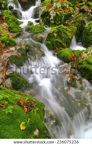 Stream of water amongst green rocks in autumn - stock photo