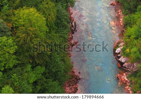 Stream of water and green vegetation at the bottom of a deep canyon - stock photo