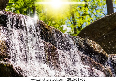 stream of water flowing along the a rock on a background greenery - stock photo