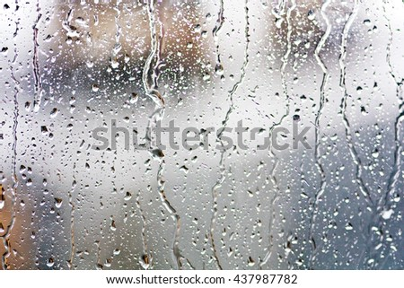 Stream of water in heavy rain. Raindrops on window pane. Blur effect. - stock photo