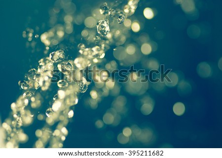 Stream of water levitating. Hovering water. Flying raindrops. Selective focus. Blurred background. Pretty art bokeh. Vintage color, instagram-like filter. Place for text - stock photo