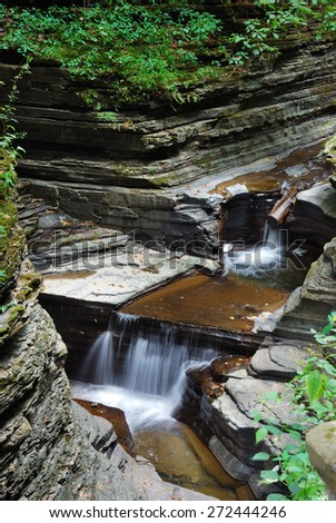 stream over rocks in woods with rocks and stream in Watkins Glen state park in New York State - stock photo