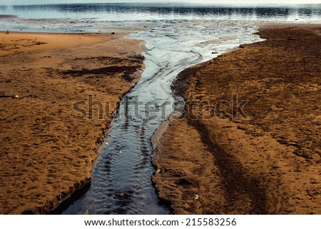 Stream running into the river - stock photo