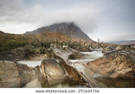 stream with flowing water and mountain at glen etive in scotland - stock photo