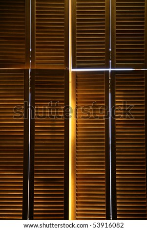 Streaming  light through the closed wooden jalousies - stock photo