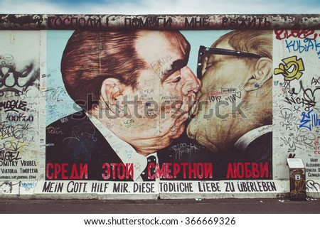 Street art graffiti painting 'The Kiss' by Dmitri Vrubel at famous East Side Gallery, the longest preserved section of Berlin wall, with retro vintage Instagram style filter effect, Berlin, Germany - stock photo