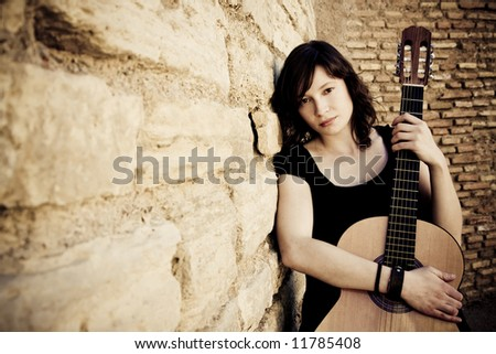 Street artist holding guitar on the wall - stock photo