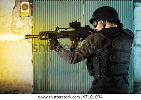 Street Assault, riot police firing his sub machine gun - stock photo