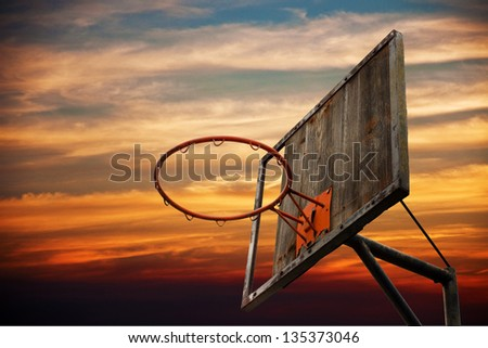 Street basketball. Old basketball hoop and a back board in sunset against the dark orange sky. - stock photo