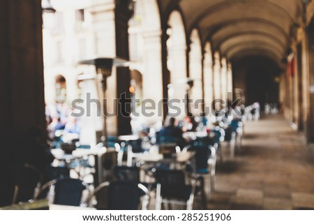 Street cafe in Barselona with square metal table and wicker chairs on the background of blurred street with people - stock photo