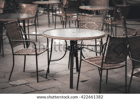 Street cafe tables and chairs in European city - stock photo