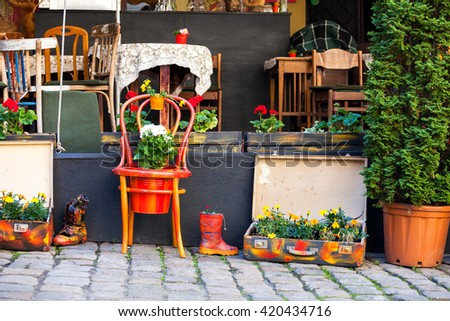 Street cafe terrace with tables and flowers in European city - stock photo