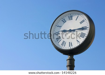 Street clock against blue sky with copy space - stock photo
