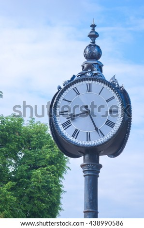Street clock on a pole against blue sky and green foliage with copy space. An old exterior clock with blue sky and clouds. Vintage clock measuring time. An Image of a antique clock with space for text - stock photo