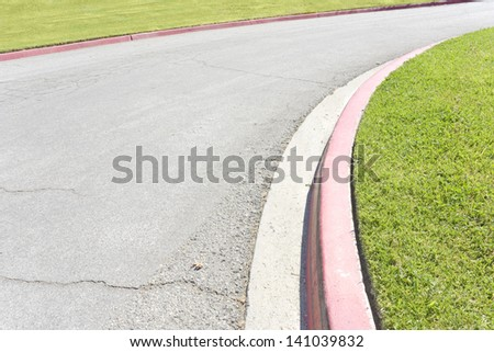Street curve and red curb. Suburban road curve turning right bordered by painted red curbs. Textured grey asphalt lined with cracks. Trimmed grass on both sides of the street. Lots of room for text. - stock photo
