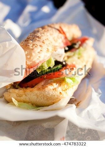 street eating greek submarine sandwich from fresh baguette