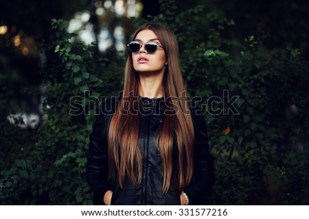 Street fashion concept - closeup portrait of a pretty girl. Wearing leather jacket, round sunglasses. Autumn woman. Artsy bohemian rock style. Fall fashion. Toned style instagram filters - stock photo