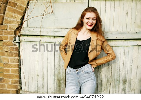 Street fashion concept - closeup portrait of a pretty hipster girl. Wearing brown leather jacket and high waisted jeans. Beautiful autumn woman with red lips and curly hair. Artsy bohemian style.