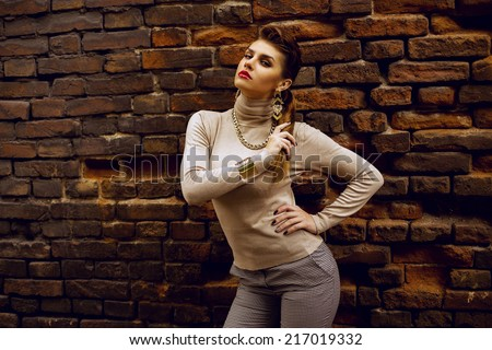 Street fashion concept. Fashion portrait of beautiful brunette in trendy casual clothes posing  over  old brick wall. Vogue style. Outdoor shot. Copy-space - stock photo