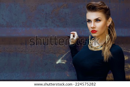 Street fashion concept. Fashion portrait of beautiful brunette in trendy casual clothes posing  over metal background. Vogue style. Outdoor shot - stock photo