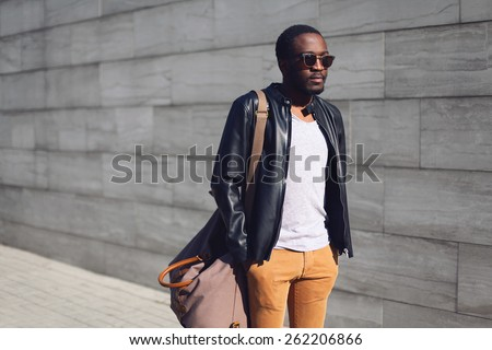 Street fashion concept - portrait stylish handsome african man standing in city against a grey textured wall evening, view profile