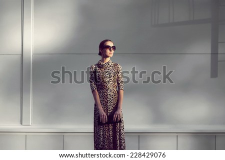 Street fashion concept - pretty elegant woman in dress with leopard print and sunglasses posing in urban style outdoors - stock photo