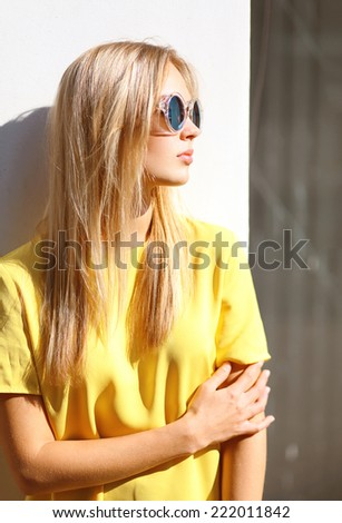 Street fashion photo, stylish pretty hipster girl in sunglasses posing in the city - stock photo