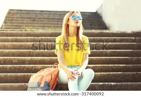 Street fashion, pretty stylish cool girl wearing a sunglasses and t-shirt with backpack in the city - stock photo