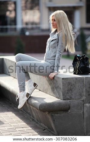 street fashion shooting. Women/girl dressed casual. White color of hair. Attractive and athletic type of body.  - stock photo