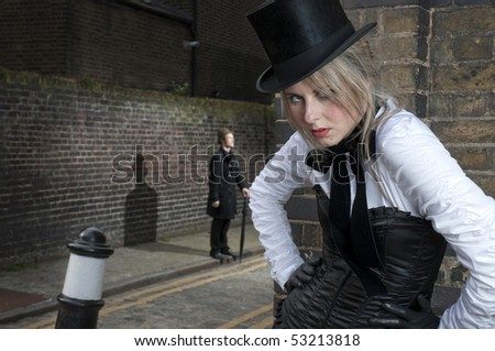 Street Fashion shot of woman in late victorian clothes with man in the background. - stock photo