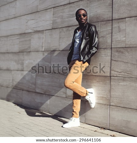 Street fashion, stylish young african man wearing a sunglasses and black rock leather jacket on evening city background